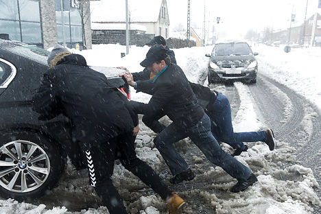 Motorists help push a car off the road in Roskilde on Sunday. Photo: Jens Astrup/Scanpix